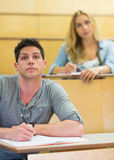 Thoughtful male student during class. At the lecture hall Stock Photography