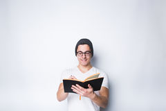 Thoughtful male student holding notebook and looking up isolated on a white background. Happy young male student holding notebook and writing down his wishes and Stock Photography