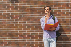 Thoughtful male student learning subject. Pensive young man is studying with seriousness. He is standing near wall and touching pencil to chin. Copy space in Royalty Free Stock Images