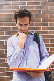 Thoughtful male student studying papers. Serious young man is reading documents from folder with concentration. He is standing and carrying backpack Royalty Free Stock Photos