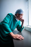 Thoughtful male surgeon looking through window Stock Images