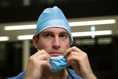 Thoughtful male surgeon wearing surgical mask. In hospital Stock Photos
