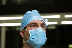 Thoughtful male surgeon wearing surgical mask. In hospital Royalty Free Stock Photo
