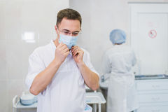 Thoughtful male surgeon wearing surgical mask in hospital.  Royalty Free Stock Images