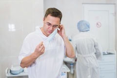Thoughtful male surgeon wearing surgical mask in hospital.  Stock Photography