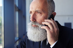 Thoughtful male talking on phone while looking out window Stock Images