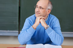 Thoughtful male teacher in class. Sitting at his desk in front of the blackboard staring off to the side Royalty Free Stock Photos