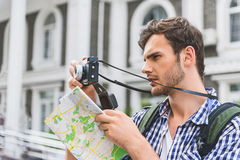 Thoughtful male tourist using camera in city Royalty Free Stock Photos