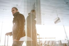 Thoughtful male waiting for plane. Low angle portrait of pensive bearded man leaning on window while standing in airport. Copy space. Trip concept Royalty Free Stock Images