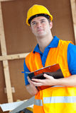Thoughtful male worker holding a clipboard. At work Stock Image