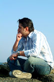 Thoughtful man. At seaside with blue sky on the background and space for text Royalty Free Stock Images