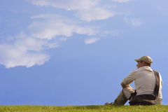 Thoughtful man. A man sitting on the grass Stock Photo