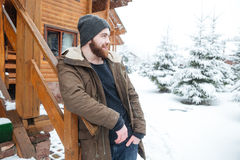 Thoughtful man with beard standing near log cabine in winter Royalty Free Stock Photo