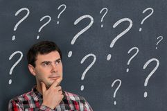 Thoughtful man and blackboard with question marks. Education concept Stock Images