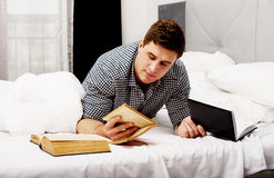 Thoughtful man with a book in his bed. Royalty Free Stock Images