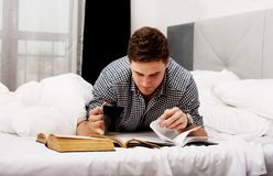 Thoughtful man with a book in his bed. Royalty Free Stock Photo