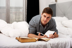 Thoughtful man with a book in his bed. Stock Photo
