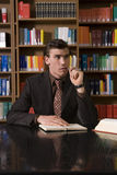 Thoughtful Man Chewing Pen At Library Desk Royalty Free Stock Images