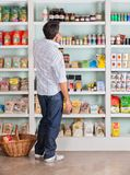 Thoughtful Man Choosing Products In Supermarket Stock Image