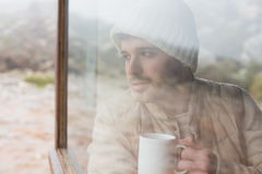 Thoughtful man with cup looking out through window. Thoughtful young man with coffee cup looking out through cabin window Stock Photos