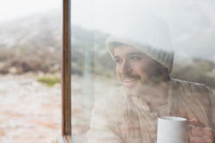 Thoughtful man with cup looking out through window. Thoughtful young man with coffee cup looking out through cabin window Stock Image