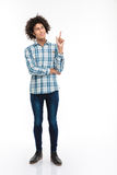 Thoughtful man with curly hair pointing finger up Royalty Free Stock Photo