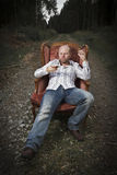 Thoughtful Man Drinking Cognac in a Vintage Chair Royalty Free Stock Image