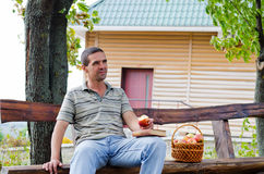 Thoughtful man eating an apple outdoors Stock Photography