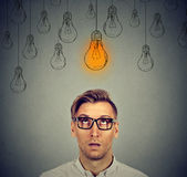 Thoughtful man in glasses with light idea bulb sign above head Royalty Free Stock Photo