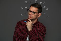 Thoughtful man with glasses and pen in his hands. Thoughtful man, a teacher with glasses and pen in his hands, thinks about something on gray background Royalty Free Stock Image