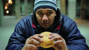 Thoughtful man is going to eat burger. Unhealthy meal. Health damage. Hunger