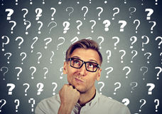 Thoughtful man has many questions no answer. Thoughtful confused handsome man in glasses has too many questions and no answer royalty free stock image