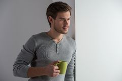 Thoughtful man having coffee and leaning on wall. Royalty Free Stock Image