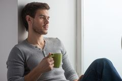 Thoughtful man having coffee and leaning on wall. Stock Images