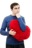 Thoughtful man holding a big red heart Royalty Free Stock Image