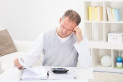 Thoughtful Man Holding Calculator Royalty Free Stock Photo