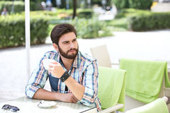 Thoughtful man holding coffee cup at sidewalk cafe Royalty Free Stock Images
