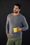 Thoughtful man holding a mug of coffee. Against black background Royalty Free Stock Images