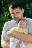 Thoughtful man holding serious baby Royalty Free Stock Photos