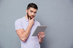 Thoughtful man holding tablet computer. Portrait of a thoughtful man holding tablet computer and looking at camera over gray background Stock Photos
