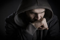 Thoughtful man with hood looking worried. Stock Image