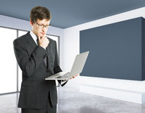 Thoughtful man with laptop. Thoughtful businessman with laptop in interior with blank blackboard. Mock up, 3D Rendering Stock Photos