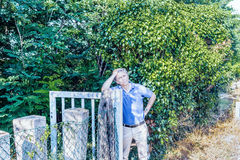Thoughtful man leaning on steel gate in countryside Stock Images