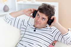Thoughtful man listening to music on the sofa Royalty Free Stock Photo
