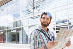 Thoughtful man looking away while holding road map against glass wall Royalty Free Stock Image