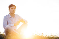 Thoughtful man looking away while sitting on grass against clear sky Stock Photos