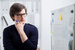 Thoughtful man looking at business charts Stock Photography