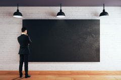 Thoughtful man looking at chalkboard Royalty Free Stock Images