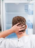 Thoughtful man looking in empty refrigerator Stock Images
