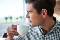 Thoughtful man looking out of the window while having coffee Stock Images